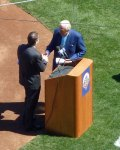 Ralph Kiner takes the microphone from Howie Rose as he prepares to introduce the Mets' starting lineup on Opening Day, 2012 (Photo credit: Paul Hadsall)