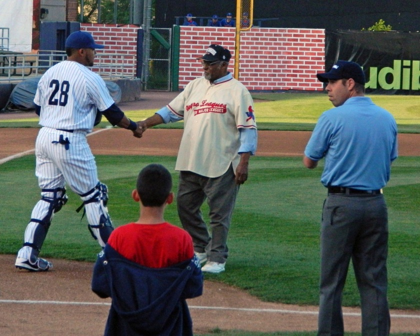 Newark Bears catcher Elvin Millan (28) shakes hands with former Negro League player Bob Scott after Scott threw out the ceremonial first pitch on Opening Day.