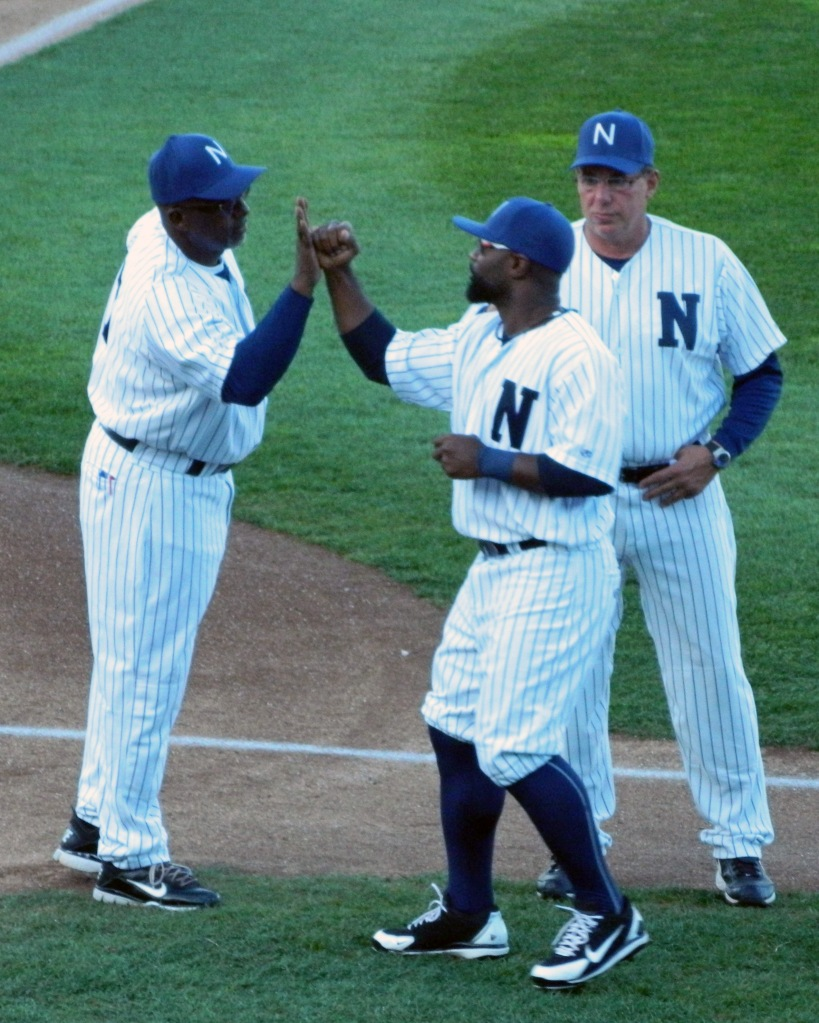 Newark Bears manager Garry Templeton (left) high fives player J.J. Sherrill as pitching coach Ralph Citarella (right) looks on. (Photo credit: Paul Hadsall)
