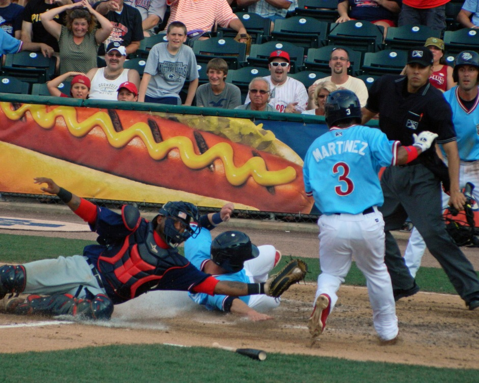 Lehigh Valley Iron Pigs catcher Steven Lerud evades the tag of Pawtucket Red Sox catcher Alberto Rosario. Miguel Martinez (3) somehow also managed to safely score on the play. (Photo credit: Paul Hadsall)