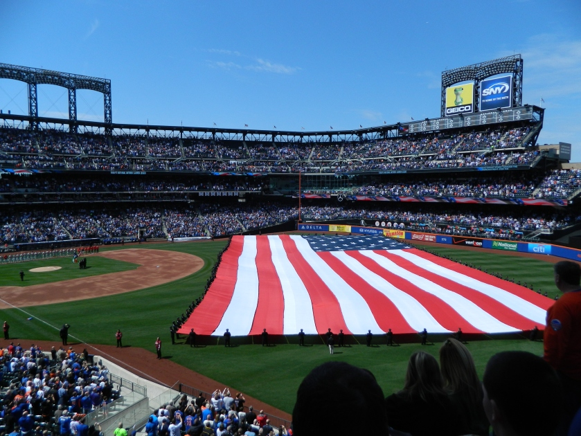 Members of the New York City Police Department unfurl a giant American flag across the outfield at Citi Field during the Mets' 2015 home opener in April (Photo credit: Paul Hadsall)